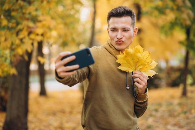 紅葉の花束を持って自分撮りをしているハンサムな男の肖像画