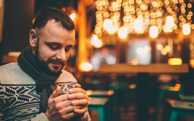 잘 생긴 남자의 초상화는 커피 컵을 들고있다.