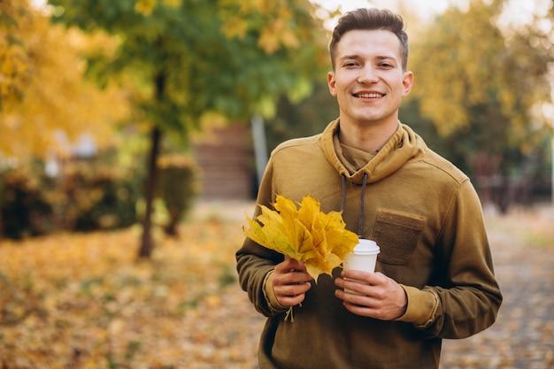 Портрет красивого парня, улыбающегося и держащего букет осенних листьев и чашку кофе