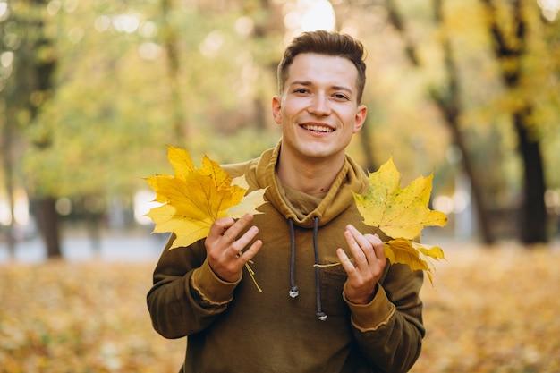 Портрет красивого парня, улыбающегося и держащего букет осенних листьев в парке