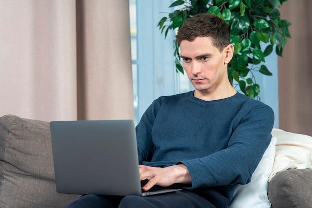Портрет красивый парень молодой человек фрилансер работает на своем портативном компьютере на диване или диване в