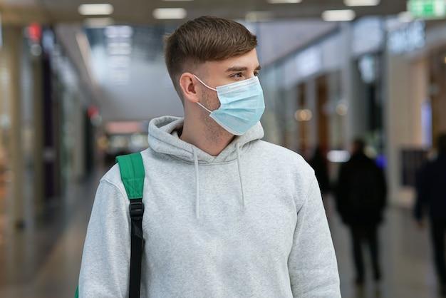 Портрет красивого парня, молодого человека в стерильной медицинской маске на лице от вируса, коронавируса