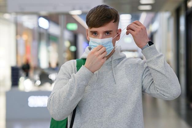Портрет красивого парня, молодого человека, надевающего стерильную медицинскую маску на лицо от вируса