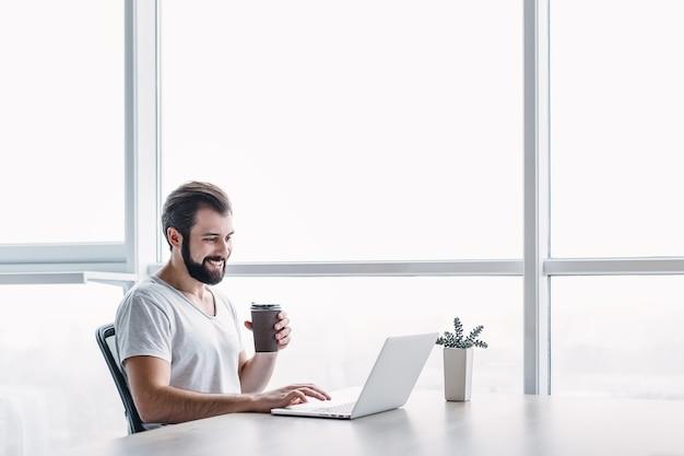 Портрет красивого счастливого бородатого молодого бизнесмена в серой футболке, сидя в офисе и перерыв с чашкой кофе. он использует свой ноутбук, глядя на экран с зубастой улыбкой.