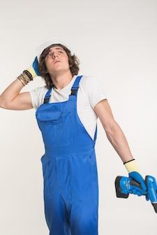Портрет красивого счастливого строителя с skrewdriver на белой предпосылке.