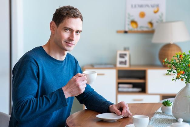 Портрет красивого счастливого позитивного парня, молодого улыбающегося человека, сидящего за столом на кухне и пьющего