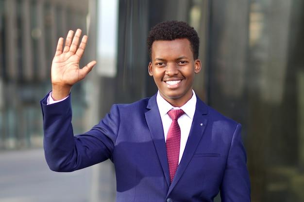 Портрет красивого счастливого положительного молодого бизнесмена в официальном костюме. черный афроамериканец афроамериканец машет рукой на открытом воздухе в офисе