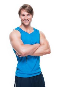 흰 벽에 포즈 블루 셔츠에 잘 생긴 행복 스포츠맨의 초상화.