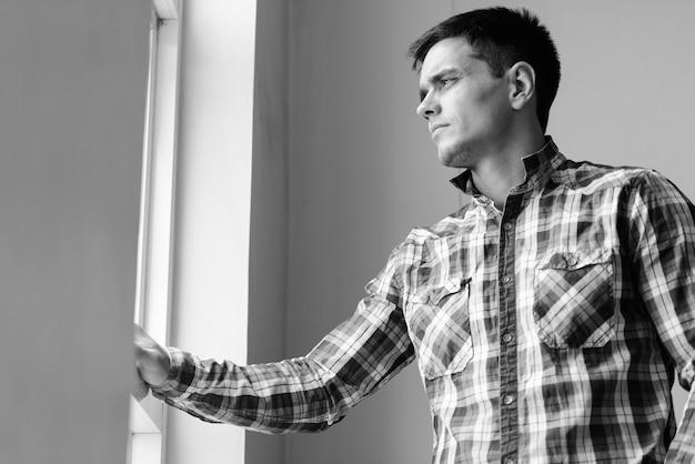 黒と白で屋内の家の窓のそばにハンサムな流行に敏感な男の肖像画