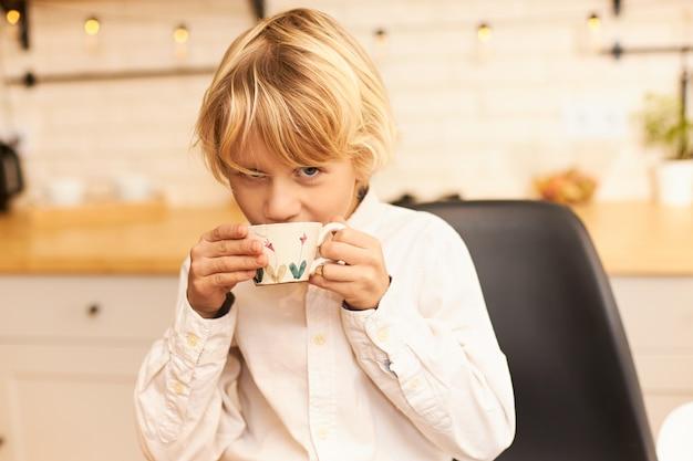 학교 전에 아침 식사를하고, 컵을 들고 부엌 카운터에기구와 화환으로 웃고있는 동안 금발 머리가 차를 마시는 잘 생긴 즐거운 소년의 초상화