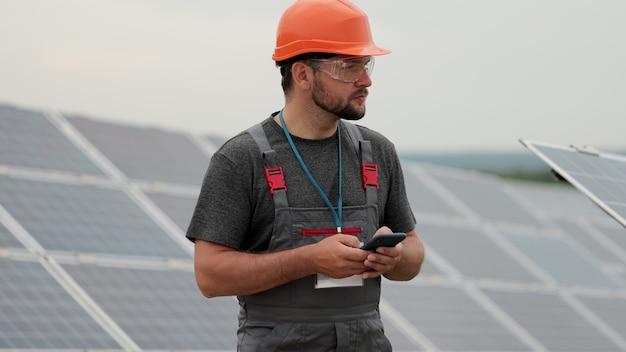 잘생긴 남성 엔지니어의 초상화는 스마트폰을 사용합니다. 배터리가 있는 행 근처에 서 있는 태양열 농장 노동자. 태양광 패널 분야. 청정 에너지 생산. 친환경 에너지.