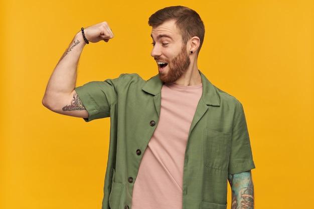 갈색 머리와 강모 잘 생긴 남자의 초상화. 녹색 반팔 재킷을 입고. 문신이 있습니다. 그의 팔뚝을 보여주고 그것을보고 흥분. 노란색 벽 위에 절연 스탠드