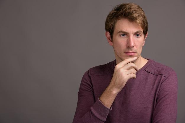 灰色の壁に対してハンサムな男の肖像
