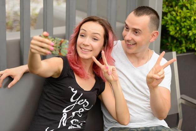 잘 생긴 남자와 야외 공원에서 사랑에 부부로 분홍색 머리를 가진 아름다운 여자의 초상화