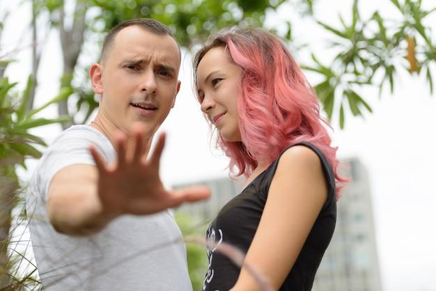 一緒に、屋外の公園で恋にピンクの髪のハンサムな男性と美しい女性の肖像画
