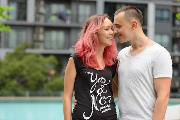 屋外のプールエリアで一緒にカップルとしてハンサムな男性とピンクの髪の美しい女性の肖像画