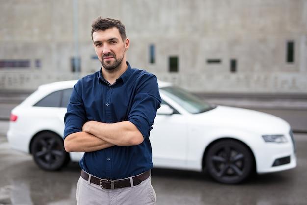 잘생긴 남자와 그의 흰색 차의 초상화