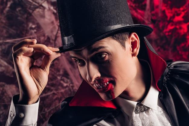 ハロウィーンのドラキュラの衣装を着たハンサムな男の肖像画。笑顔の吸血鬼