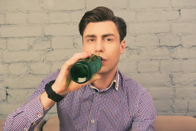 ビールを飲み、家でサッカーを見ているハンサムな男の肖像画