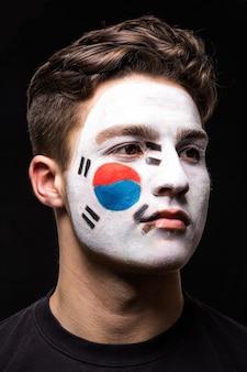 검은 배경에 고립 된 페인트 플래그 얼굴로 대한민국 대표팀의 잘 생긴 남자 얼굴 팬 팬의 초상화. 팬들의 감정.