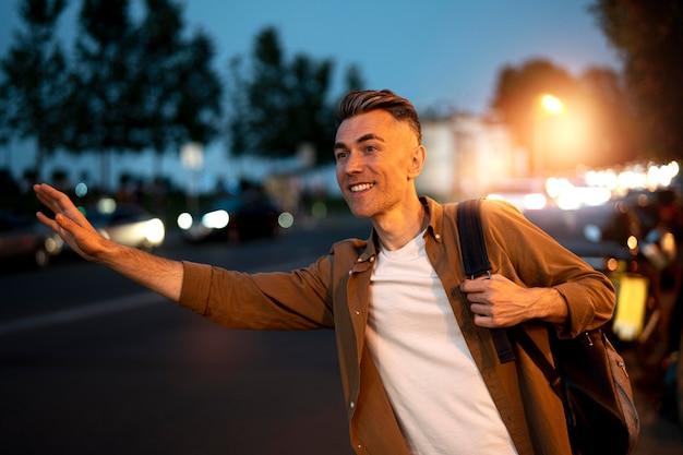 도시에서 밤에 택시에 대한 환영 잘 생긴 남자의 초상화
