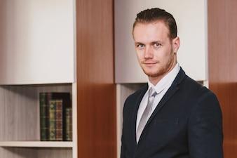 Portrait of handsome man in black suit standing in office