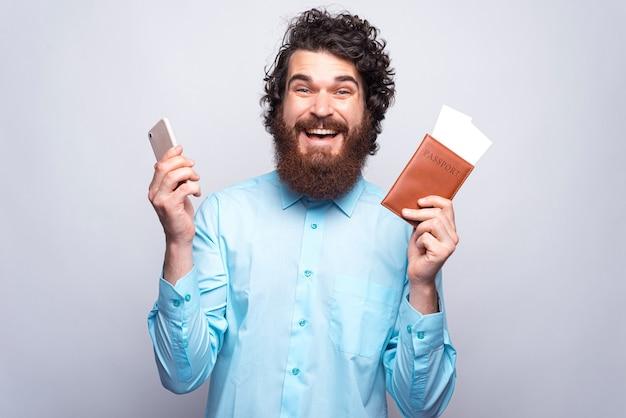 캐주얼 웃고 여권과 스마트 폰을 들고 잘 생긴 남자의 초상화, 온라인 티켓 구매