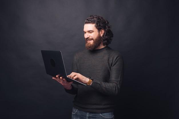 검은 벽에 노트북을 사용하는 캐주얼에 잘 생긴 남자의 초상화