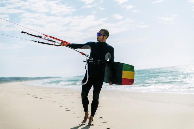 해변에서 잘 생긴 남자 kitesurfer의 초상화입니다.