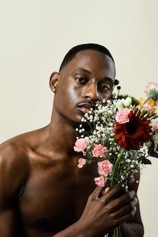 Портрет красивого мужчины позирует с букетом цветов