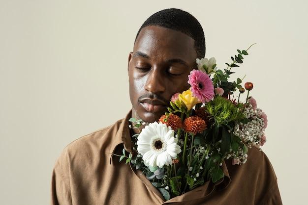 꽃의 부케와 함께 포즈를 취하는 잘 생긴 남자의 초상화