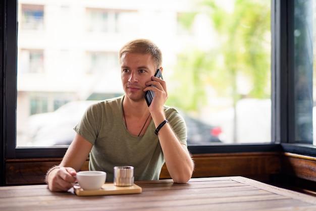 コーヒーショップでリラックスしたハンサムな男の肖像画