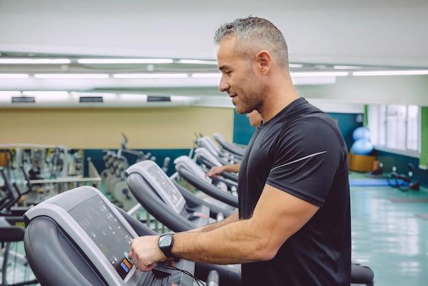 피트니스 센터에서 훈련하기 위해 러닝머신의 제어판을 설정하는 잘생긴 남자의 초상화. 스포츠 및 기술 개념입니다.