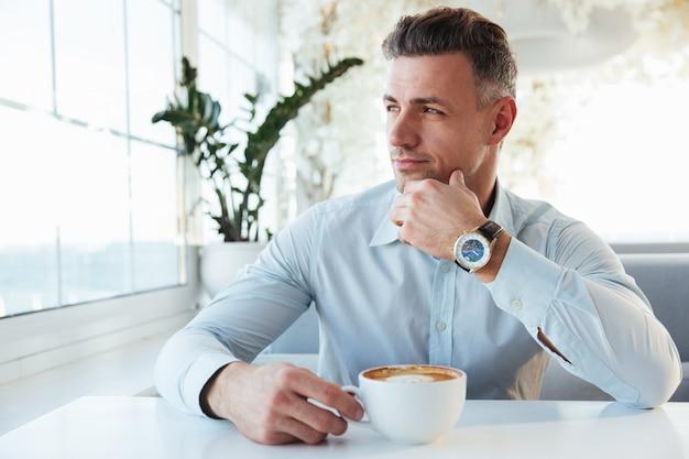Портрет красивого человека, сидящего в одиночестве в городском кафе с чашкой капучино, смотрящего в сторону с задумчивым взглядом и трогательным подбородком