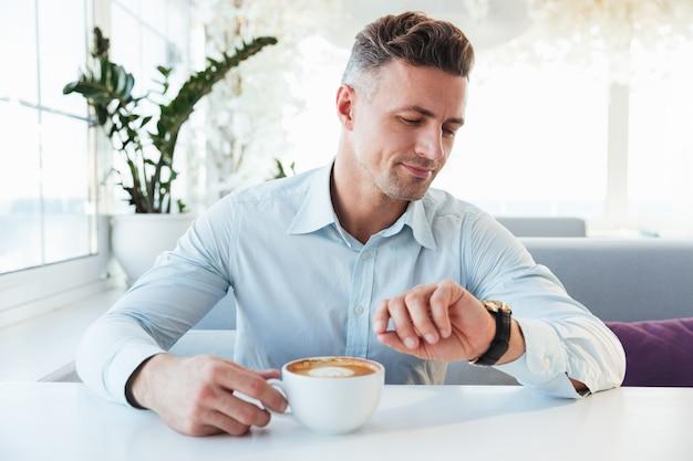 Портрет красивого человека, сидящего в одиночестве в городском кафе с чашкой капучино, смотрящего на наручные часы и ожидающего встречи