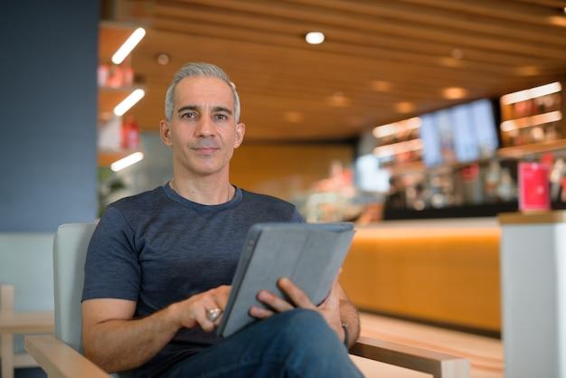 디지털 태블릿을 들고 복사 공간이 있는 카메라 수평 샷을 보면서 커피숍에 앉아 있는 잘생긴 남자의 초상화