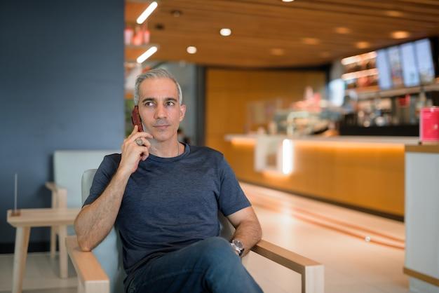 휴대 전화 가로 샷에 대해 이야기하면서 커피 숍에 앉아 잘 생긴 남자의 초상화