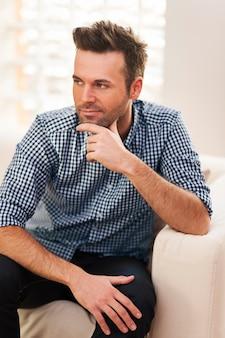 Портрет красивого мужчины, сидящего на диване