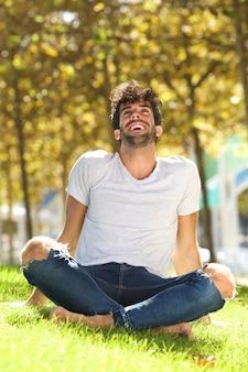 笑って腰を傾けて芝生の外に座っているハンサムな男の肖像