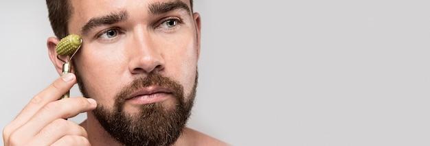 Портрет красивого мужчины, использующего ролик для лица с копией пространства
