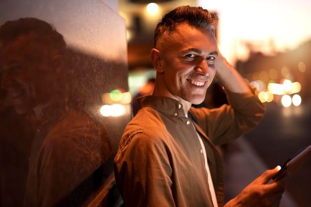 도시의 불빛에 밤에 태블릿을 사용하는 잘 생긴 남자의 초상화