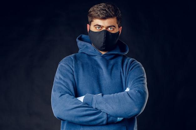 暗い壁でポーズウイルスの流行の封鎖中に顔に医療の黒いマスクを着ているハンサムな男の肖像。閉じる。