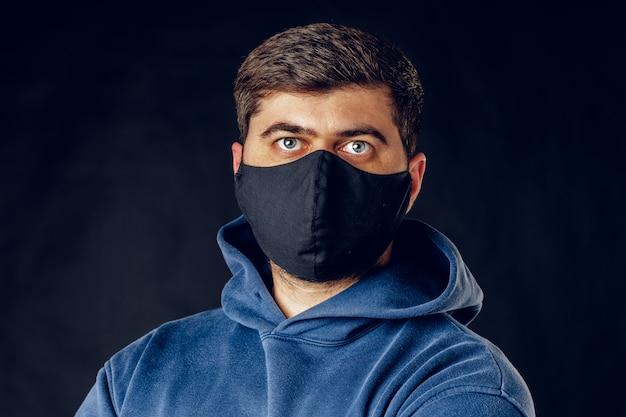ウイルスの流行の封鎖中に顔に医療の黒いマスクを着ているハンサムな男の肖像