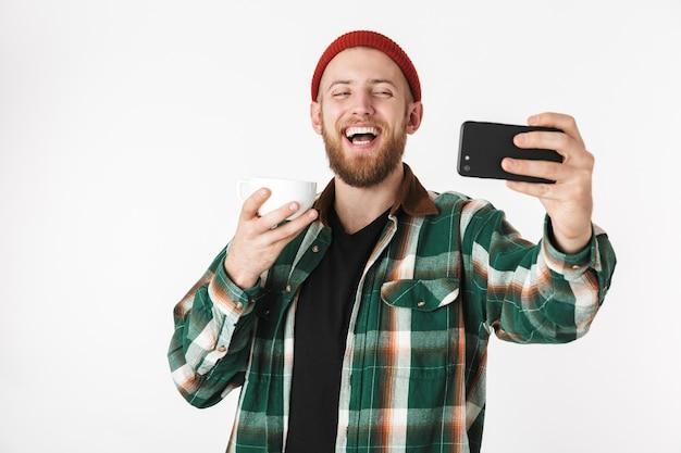 흰색 배경 위에 격리 서있는 동안 신용 카드와 휴대 전화를 들고 격자 무늬 셔츠를 입고 잘 생긴 남자의 초상화