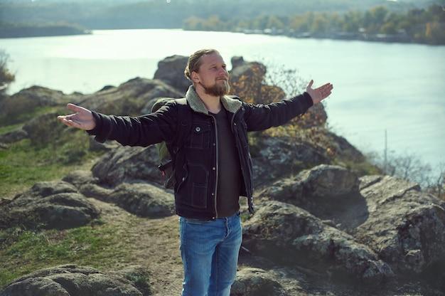 두 팔을 벌리고 호수보기를 즐기는 잘 생긴 남자의 초상화. 아름다운 자연을 즐기는 팔을 뻗은 빨간 머리 수염 남자.