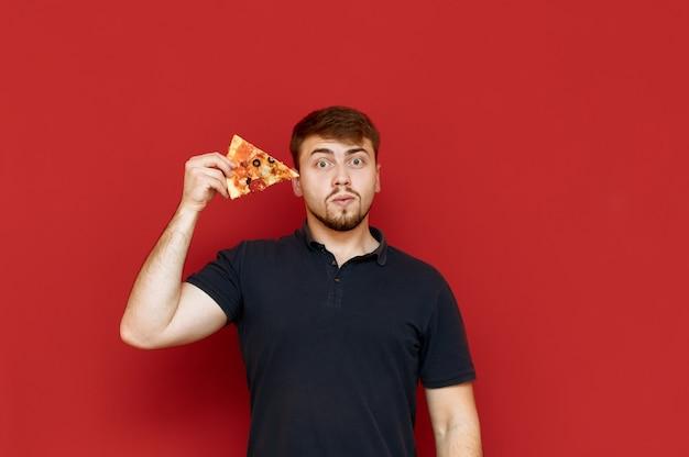 수염을 가진 잘 생긴 남자의 초상화는 그의 손에 피자 조각으로 서