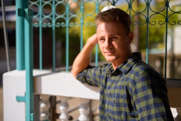 自宅の屋外で緑の市松模様のシャツを着ている金髪の巻き毛を持つハンサムな男の肖像画