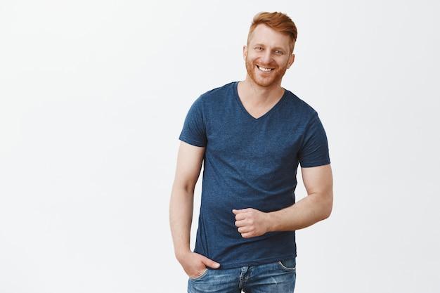 青いtシャツを着たハンサムな男性の赤毛の男性の肖像画、身振りで示すと広く笑顔
