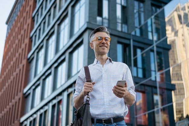 カメラ目線メッセンジャーバッグを保持しているハンサムな成熟した実業家の肖像画