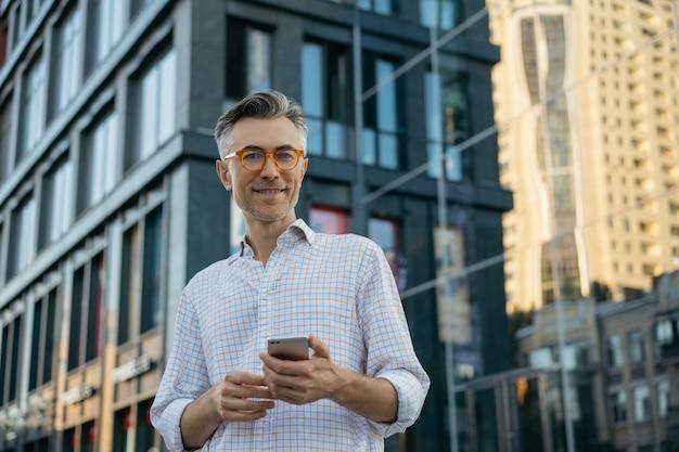 カメラ目線のスタイリッシュな眼鏡を着ているハンサムな成熟した実業家の肖像画